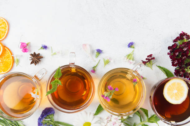 Herbal Teas Directly above view of a four tea cups with different herbal teas. Anise, flowers and dried orange slices are spread around the tea cups on white background. One of the teas has a lemon slice. greentea stock pictures, royalty-free photos & images