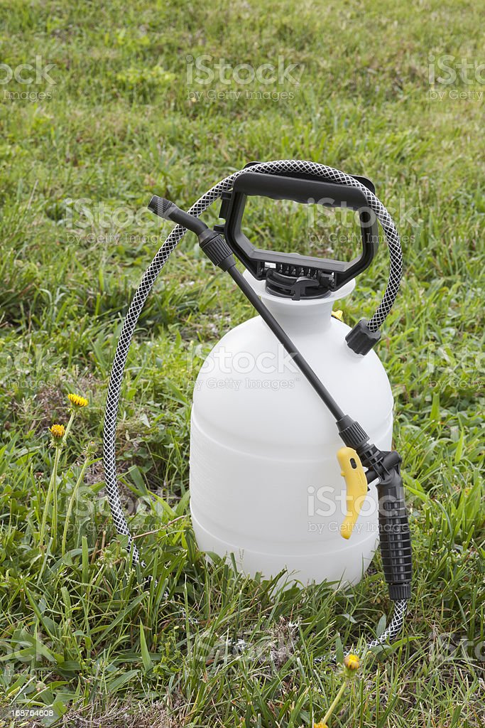 Herbicide or pesticide sprayer sits on grass in a yard stock photo