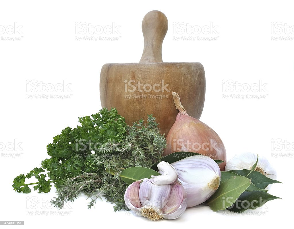 herbs and onions garlic with a wooden pestle stock photo