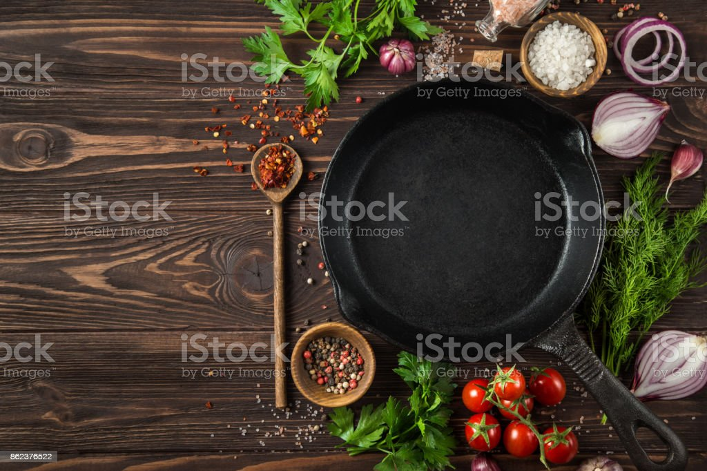 herbs and spices around cast iron skillet stock photo