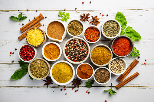 Herbs and spices in bowels over white wooden background. Top view with copy space
