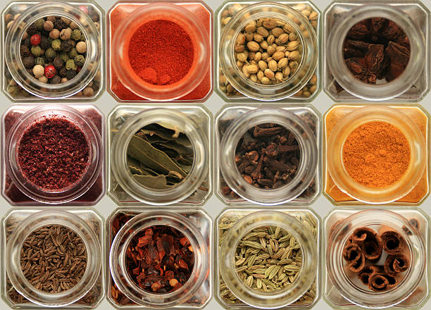 herbs and spices in glass jars stock photo