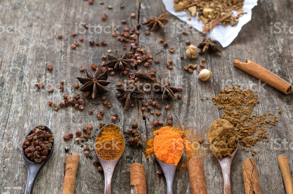 Herbs and spices on a wooden board. Spice spoon. stock photo