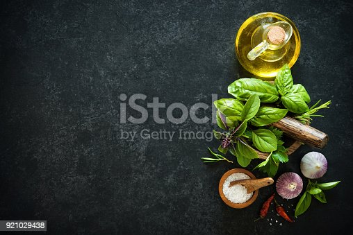 Herbs and spices on black stone table. Ingredients for cooking. Top view with copy space
