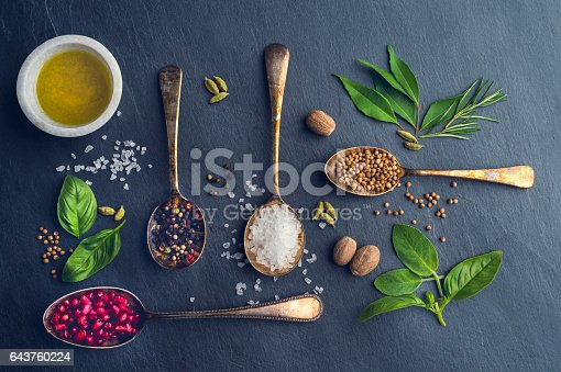 Herbs and spices on slate. High angle view with salt; pepper and a variety of ingredients