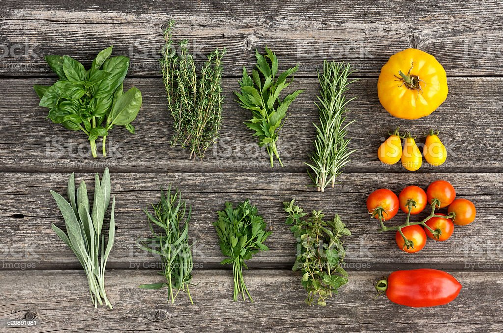 Herbs and tomatos on the wooden board stock photo