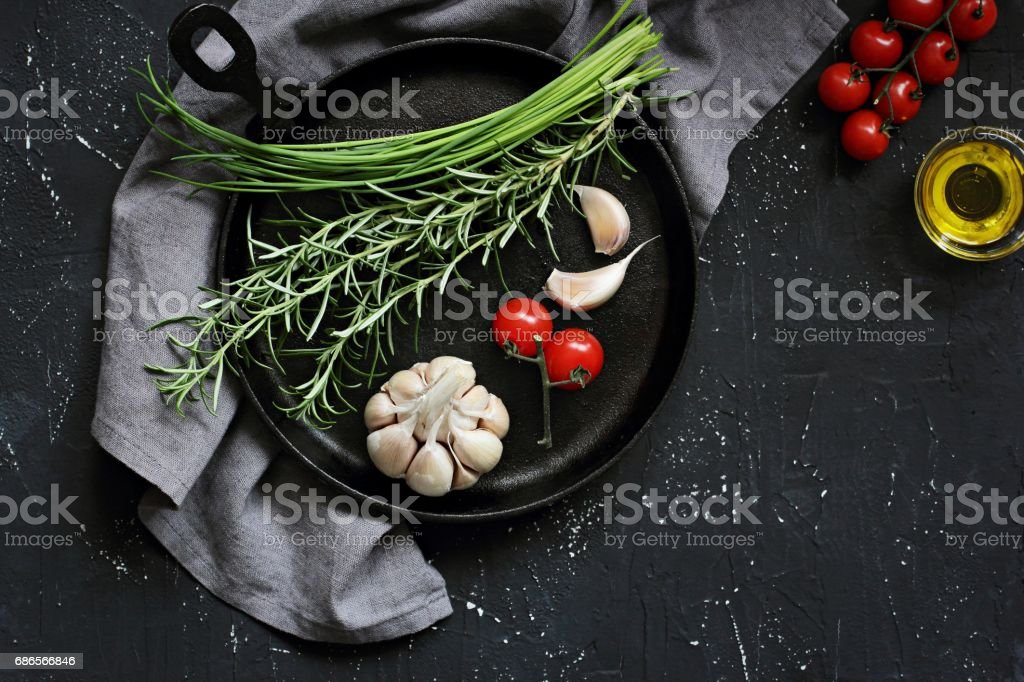 Herbs and vegetables on rustic cast iron pan over dark background. foto stock royalty-free