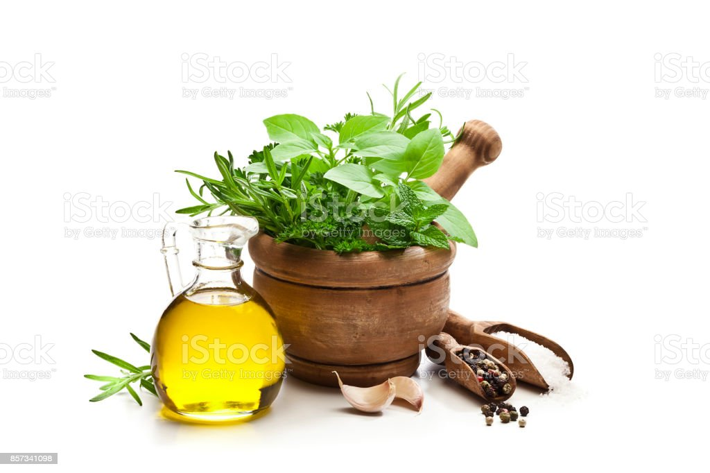 Herbs in mortar, olive oil, salt, pepper and galic isolated on white background stock photo