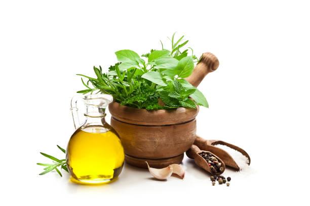 herbs in mortar, olive oil, salt, pepper and galic isolated on white background - liść mięty przyprawa zdjęcia i obrazy z banku zdjęć
