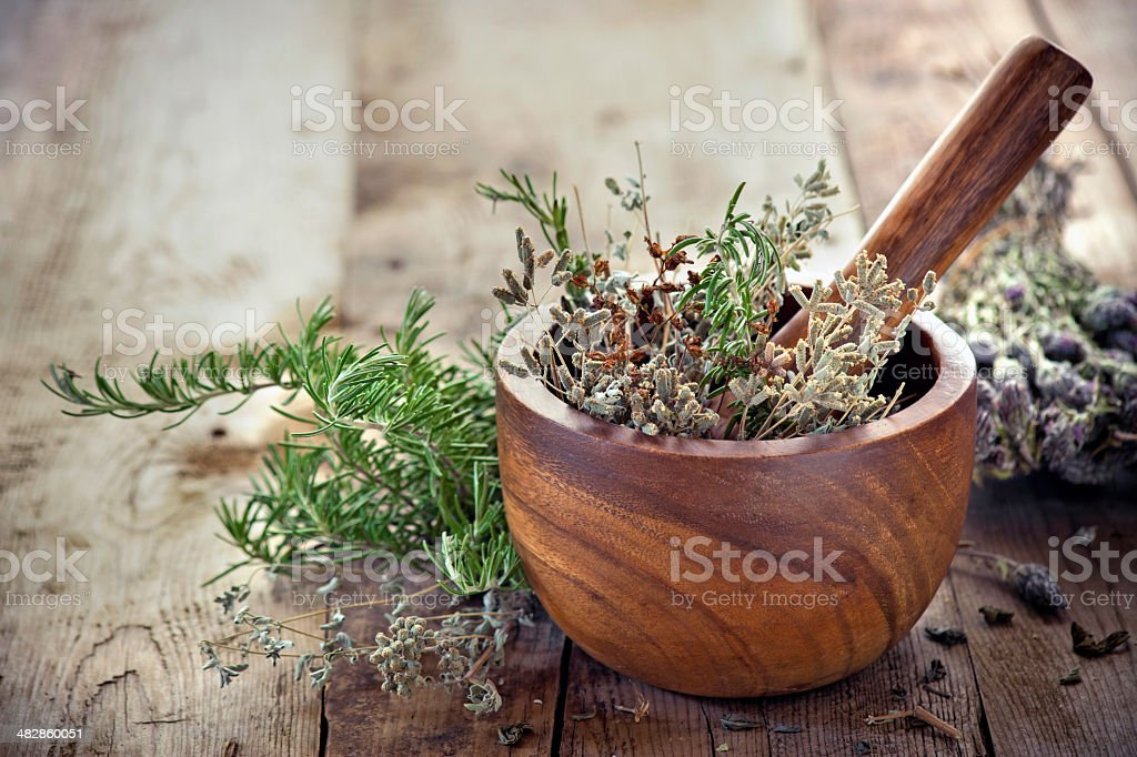 Herbs in mortar with pestle on the table stock photo