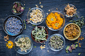 Various dried medicinal herbs and herbal teas in several bowls on blue wooden background from above