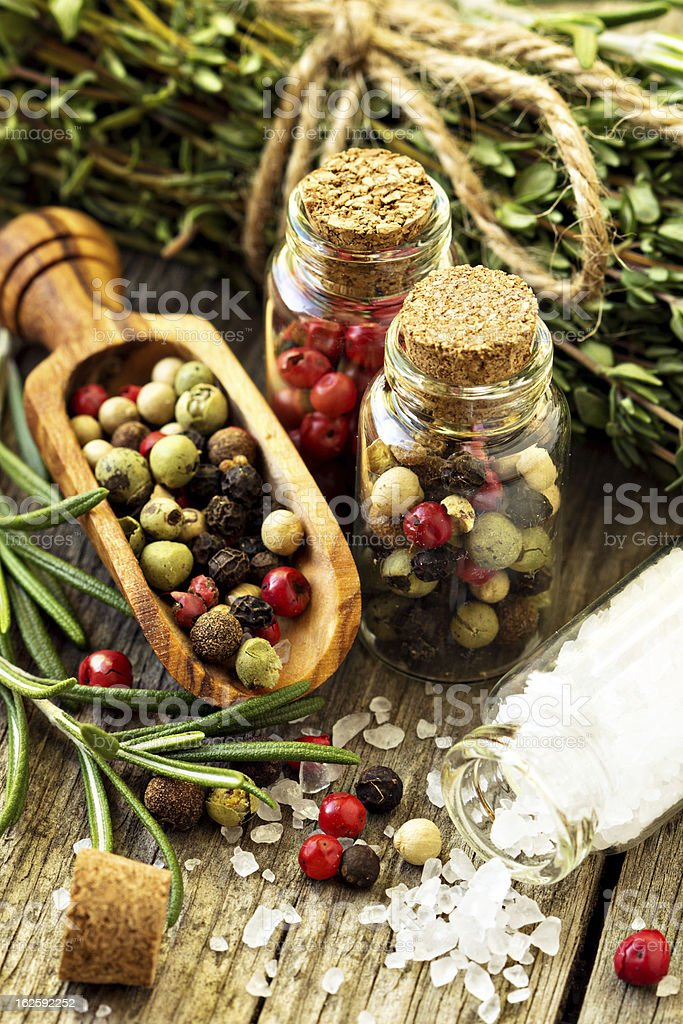 Herbs, salt and different kinds of pepper on wooden table royalty-free stock photo