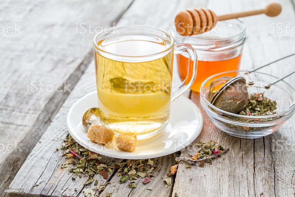 Herbsl tea in glass cup, honey, rustic wood background stock photo