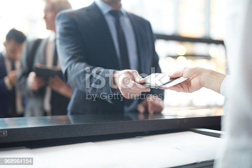 Hand of passenger giving his documents dor check-in to manager by counter