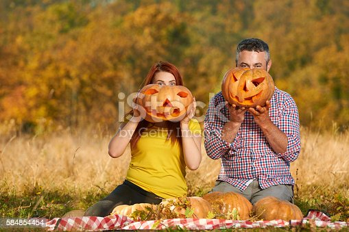 lifestyle shot of couple holding Halloween pumpkins, looking at camera and waiting for their favourite holiday.