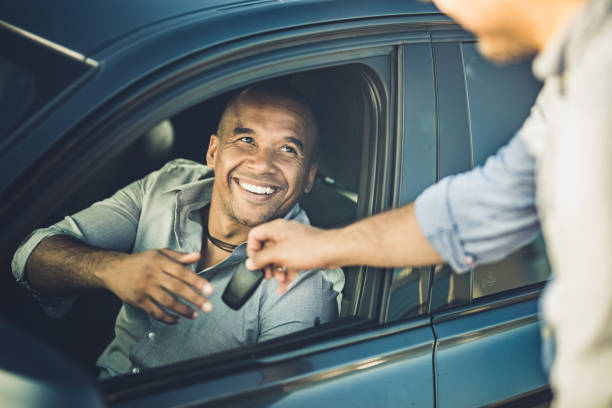 Here are the keys for your new car! Happy African American businessman taking car keys from a sales person. car key stock pictures, royalty-free photos & images