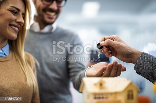 Close up of unrecognizable real estate agent giving home key to happy couple.