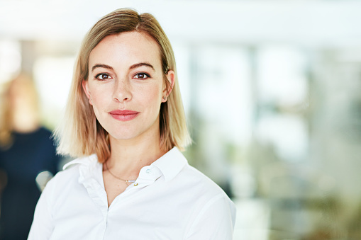 Portrait of an ambitious young woman standing in a modern office with her colleagues in the background