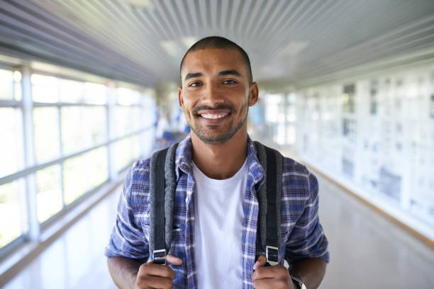 Here to secure my future Portrait of a happy young man standing in a corridor on campus adult student stock pictures, royalty-free photos & images
