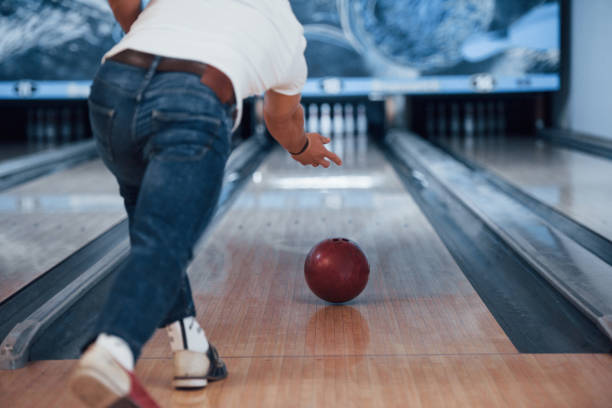 Here we go. Rear particle view of man in casual clothes playing bowling in the club stock photo