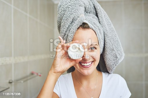 Portrait of an attractive young woman applying moisturizer to her face at home