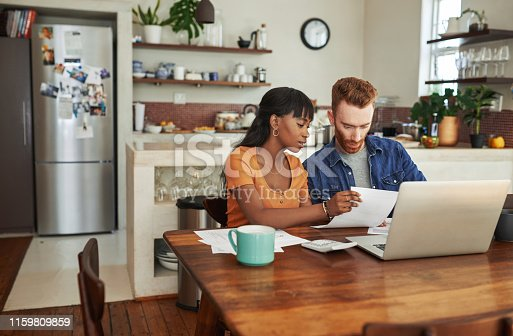 Cropped shot of a couple looking at paperwork while sitting with their laptop