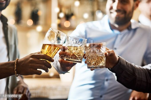 Cropped shot of a group of cheerful young friends having a celebratory toast with their drinks inside of a bar at night