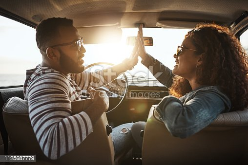 Shot of a young couple giving each other a high five on a road trip