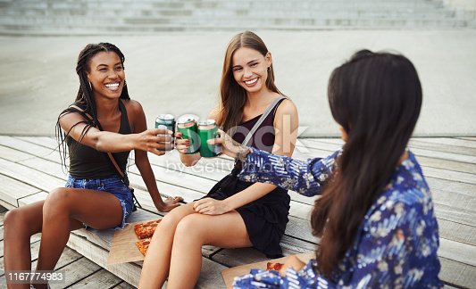 Cropped shot of three attractive young friends having a toast while sitting on the deck by the canal