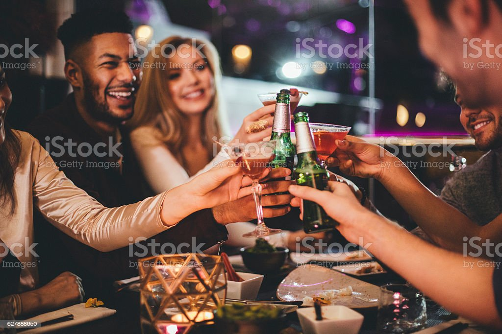 Here's to the New Year! Group of friends clinking glasses while enjoying an evening meal in a restaurant on New Years Eve. 20-29 Years Stock Photo