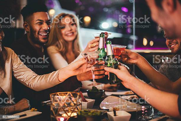 Group of friends clinking glasses while enjoying an evening meal in a restaurant on New Years Eve.
