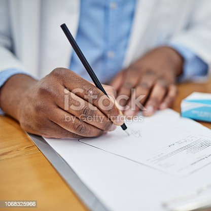 Closeup shot of an unrecognizable medical doctor filling in a prescription for medication