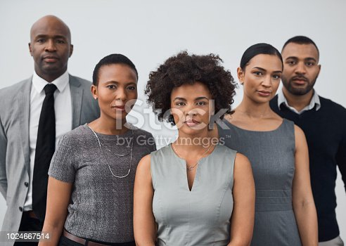 Studio portrait of a group of businesspeople standing together against a gray background