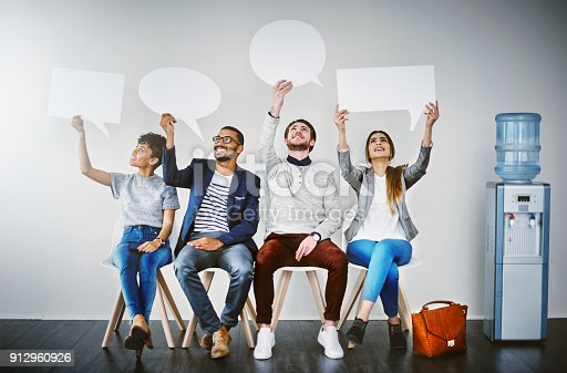 Shot of a diverse group of businesspeople holding up speech bubbles while they wait in line
