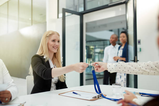 Here's your access card Shot of a cheerful businesswoman handing over a access card to a client to attend a seminar during the day security pass stock pictures, royalty-free photos & images