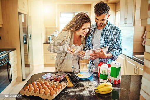 Shot of a young couple mixing ingredients in their kitchen