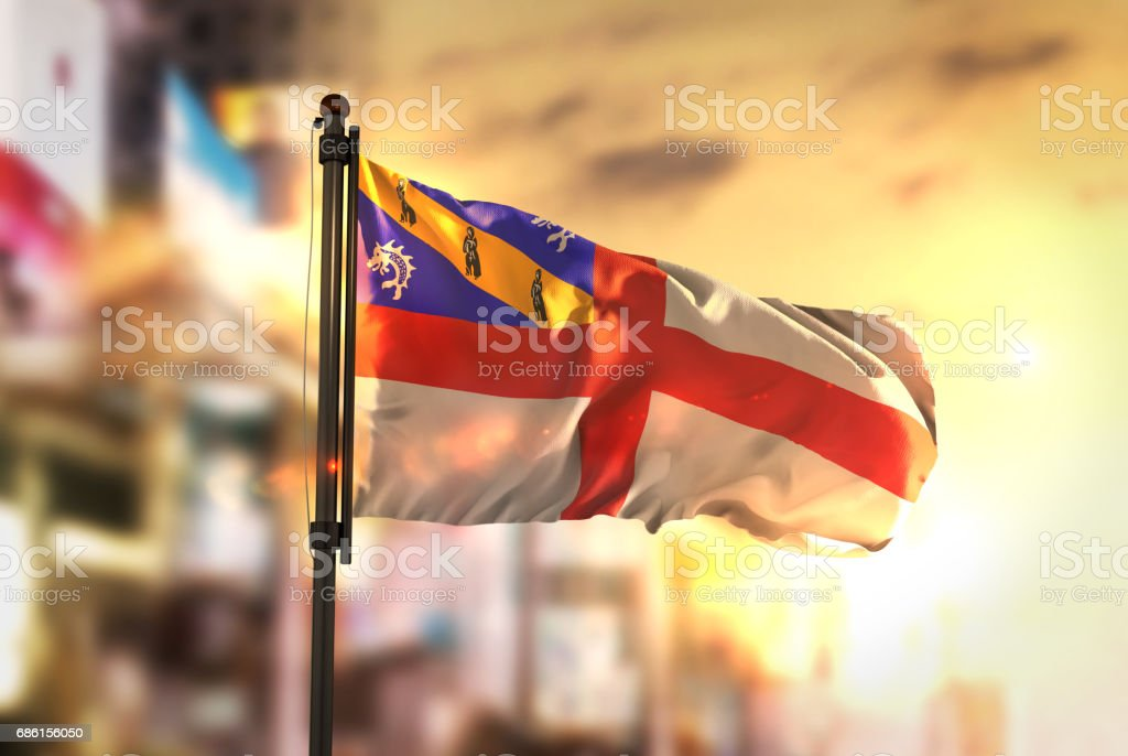 Herm Flag Against City Blurred Background At Sunrise Backlight stock photo
