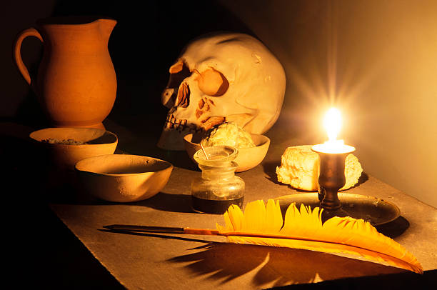 Hermetic Thoughts at Candlelight. On the table there is a lit candle, a skull, a crust of dry bread, some ceramic bowls, a pitcher, an inkwell, a feather pen. In the bowl before the skull it is visible some sulphur; in the others there are salt and mercury. They are all alchemical symbols inviting to reflection to go deeply self inside and discover the real meaning of life. arcane stock pictures, royalty-free photos & images