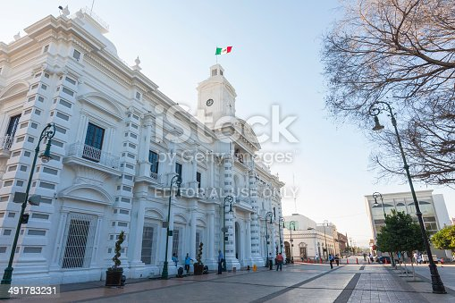 Hermosillo, Mexico - October 21, 2011: Downtown Hermosillo, view of the government palace, located in Plaza Zaragoza in front of the city's cathedral, early in the morning, with some passersby in the street.