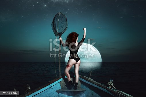 rear view of surreal hero woman in fetish wear holding fish net and looking at the moon.power, violence and fantasy.
