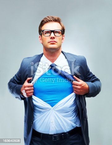 A studio shot of a determined businessman ripping open his shirt and exposing a costume underneath