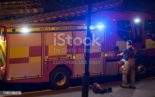 Castleford,West Yorkshire,UK - September 25th 2020 .Firefighter getting suited up with equipment beside a fire engine or fire truck at the scene of a car fire.