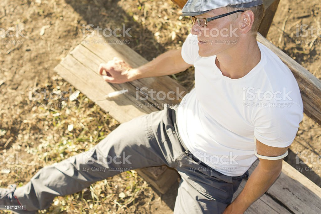 Heroin addict feeling sick in a warm sunny day royalty-free stock photo
