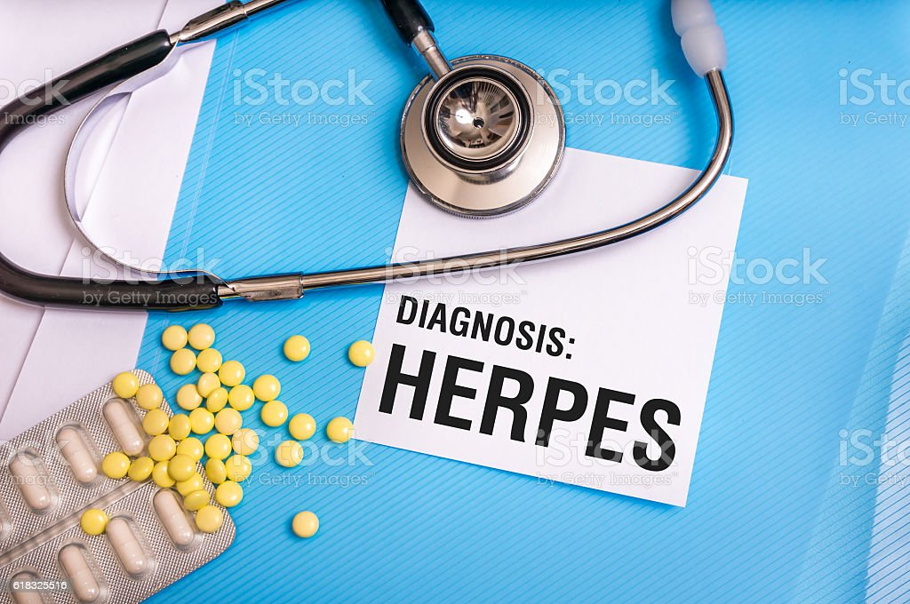 Herpes word written on medical blue folder with patient files stock photo