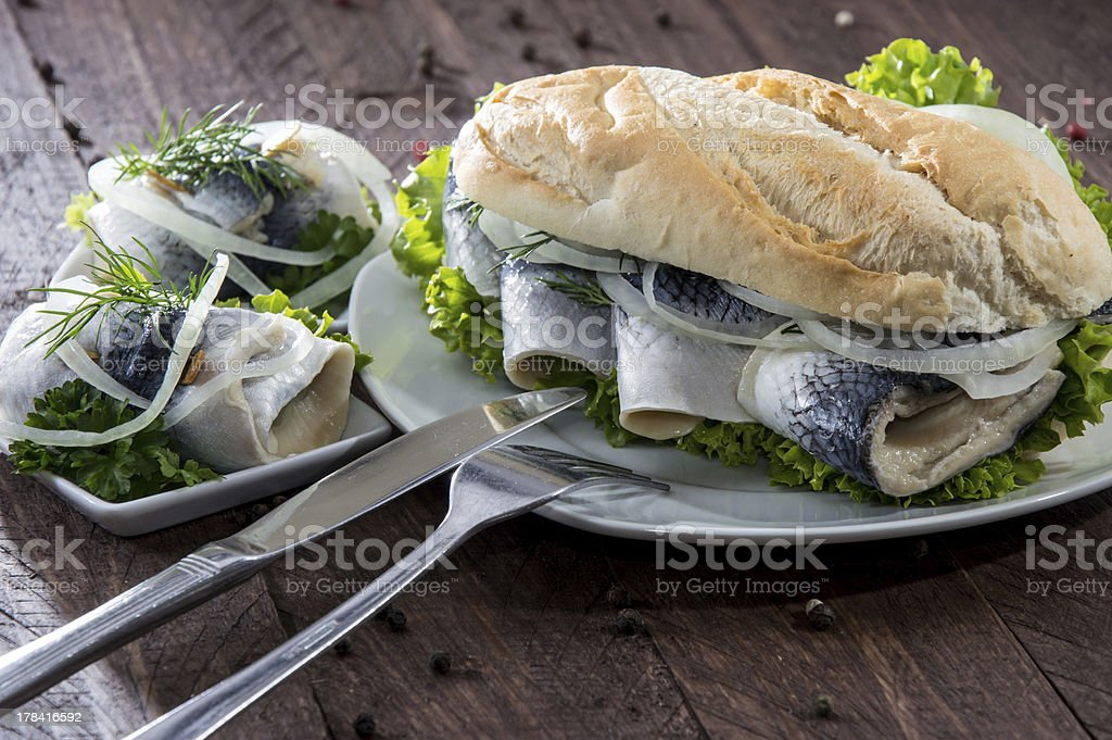 Herring Filet on a baguette (against wood) stock photo