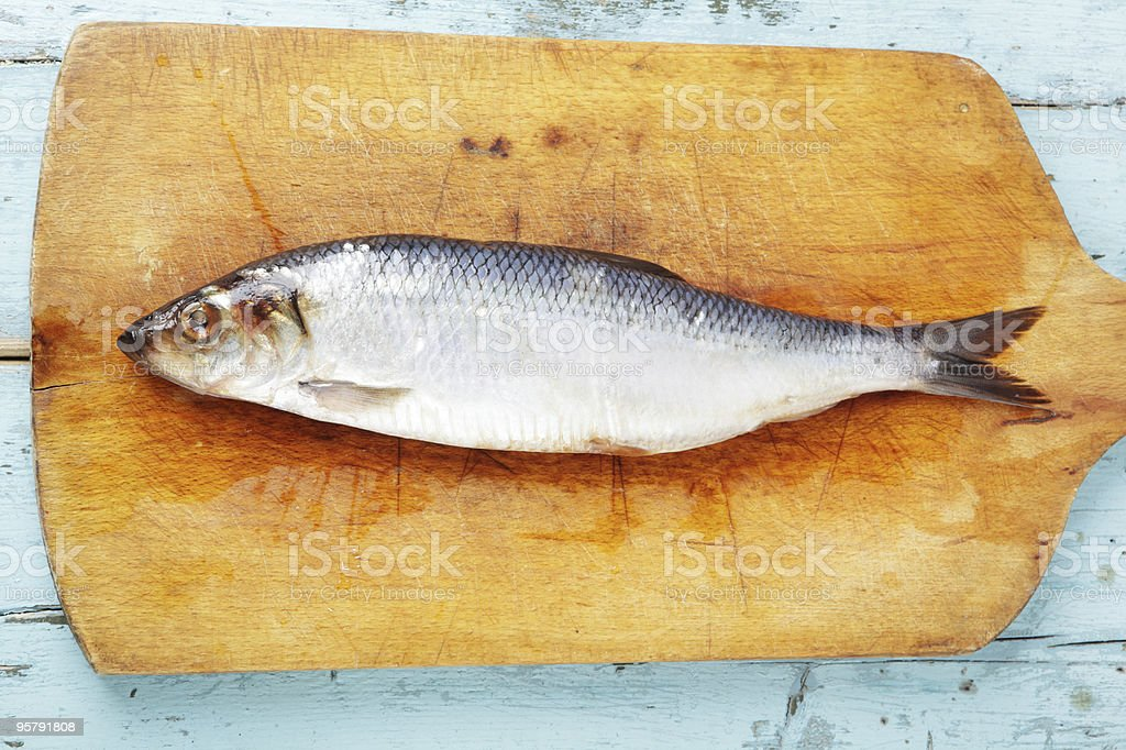 Herring on wooden chopping board on pale blue wooden table stock photo