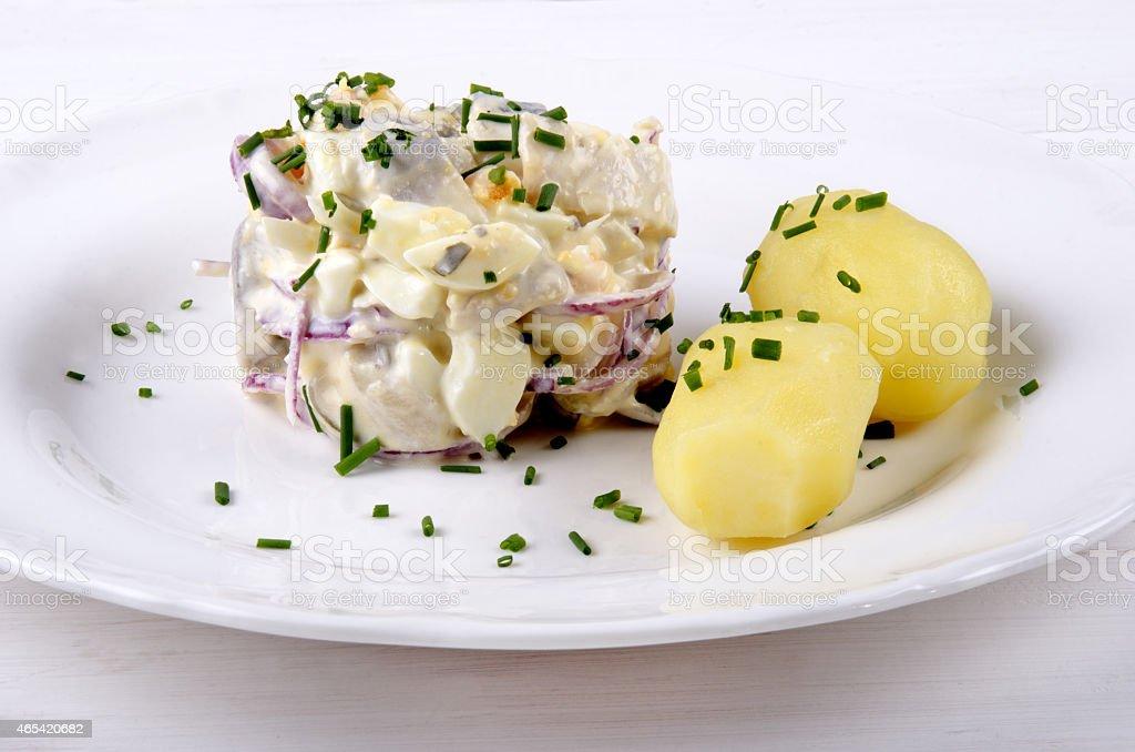 herring salad with jacket potatoes stock photo