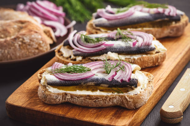 herring sandwiches with pickled cucumber. - herring stock photos and pictures