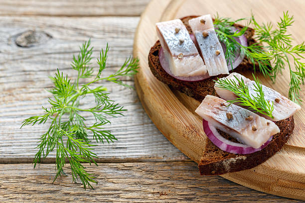 herring spiced salting and a slice of rye bread. - herring stock photos and pictures