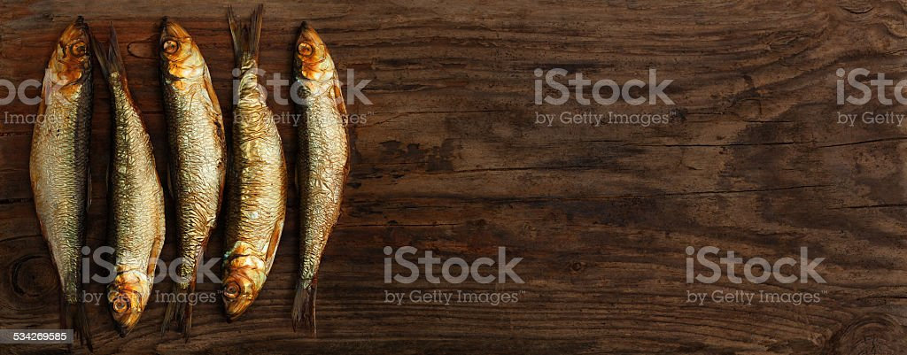 herring sprats smoked wooden oak background stock photo